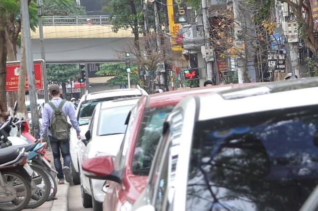 Người đi bộ phải luồn lách qua hàng dài điểm trông giữ xe có thu phí do Sở GTVT Hà Nội cấp trên đường Nguyễn Khang (Cầu Giấy - Hà Nội).