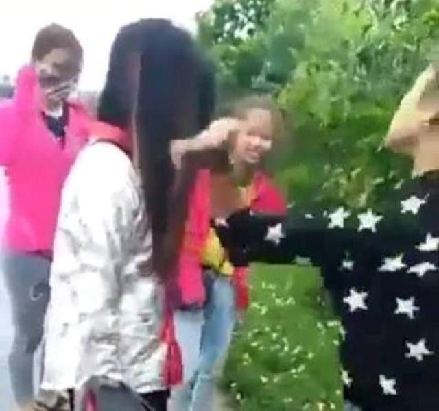 Nữ sinh mặc áo chống nắng đứng im bị hai bạn nữ (mặc áo đen, áo đỏ) tát liên tiếp vào mặt. Ảnh: Cắt từ clip