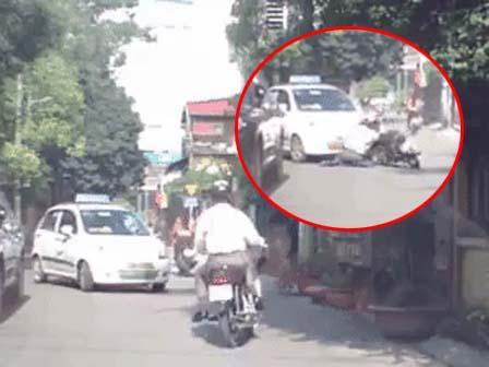 Giật mình vì tiếng chó sủa, người đàn ông chạy xe máy phi thẳng vào đâu xe taxi. Nguồn: Otofun