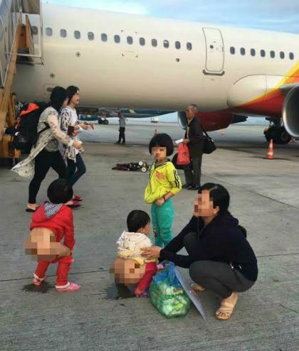 Hình ảnh người phụ nữ cho trẻ tè ngay ở lối ra cửa máy bay khiến không ít người thấy phản cảm. Ảnh: Facebook.