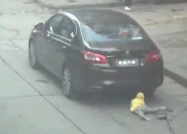 Bé gái nhỏm dậy sau khi bị ngã dưới gầm chiếc xe hơi.