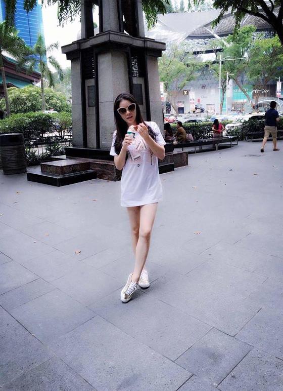 Lý Nhã Kỳ lựa chọn váy cotton trắng kết hợp giày sneaker bạc khoe đôi chân dài thon thả, nuột nà ra phố.