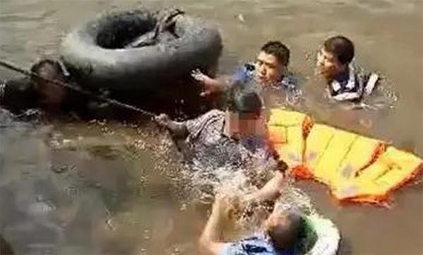 Bốn người đàn ông khỏe mạnh hợp sức giải cứu một ông lão (che mặt) nhảy sông tự tử.