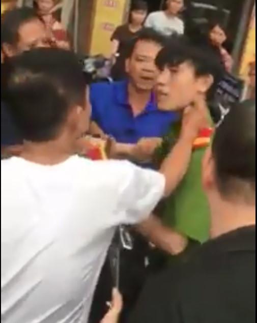 Nam thanh niên bị người dân túm áo, đánh trên phố. Ảnh cắt từ clip.