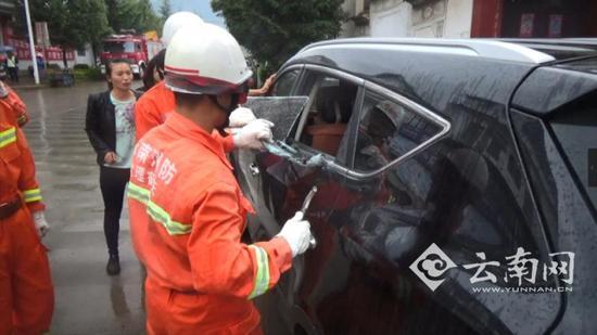 Nhân viên cứu hộ đập vỡ cửa kính ở phía cách xa bé trai nhất.
