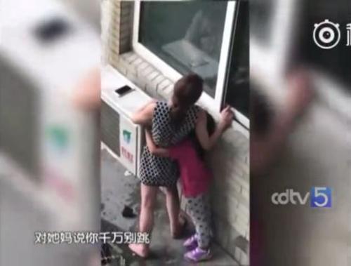 Bé gái ôm chặt lấy mẹ cầu xin mẹ đừng hành động dại dột.