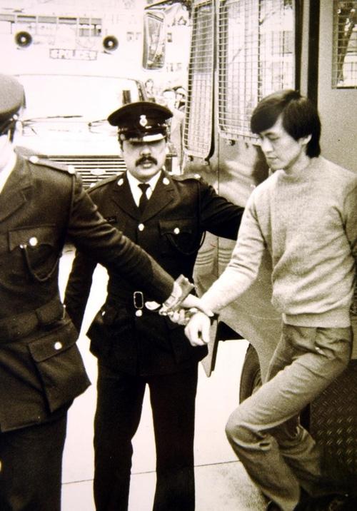 Lam Kor-wan bị cảnh sát áp tải ra khỏi xe đến nơi xét xử.