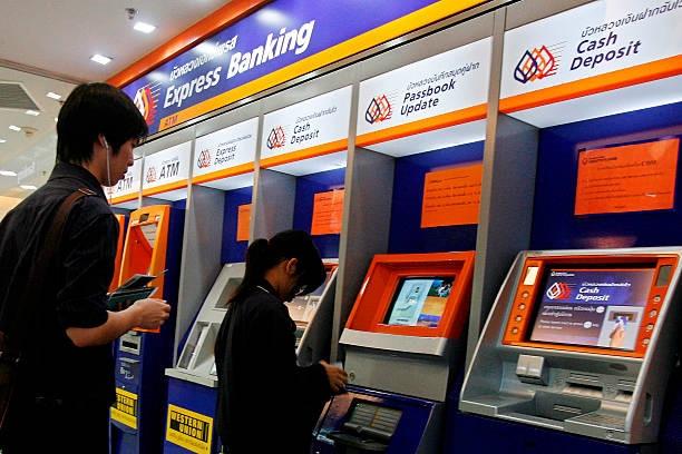 Khách hàng rút tiền từ máy rút tiền tự động ATM của Ngân hàng Bangkok tại Trung tâm thương mại MBK ở Bangkok, Thái Lan, ngày 19/1/2011. Ảnh: Bloomberg/Getty.