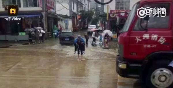 Cụ ông lần mò từng bước đưa vợ qua con phố ngập nước.