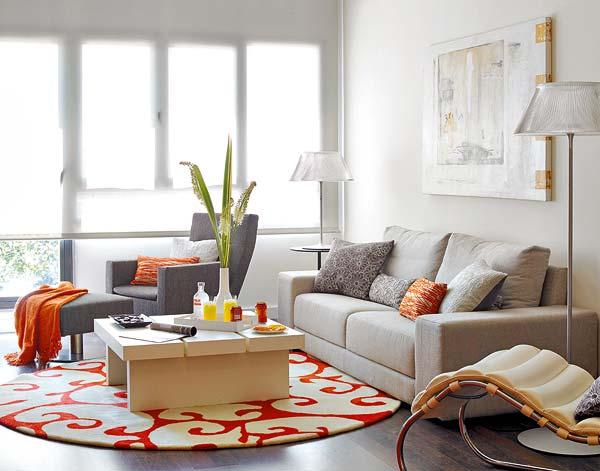 Với kiểu nhà như này, không gian phòng khách sẽ trở nên nổi bật hơn cả. Được đặt ở sát khung cửa kính, phòng khách hiện lên chan hòa ánh sáng. Cách phối màu tươi sáng với màu trắng của tường, đồ nội thất trắng xám làm chủ đạo. Nổi bật giứa không gian phòng khách là một chiếc thảm có họa tiết màu đỏ trắng tươi tắn, càng bắt sáng tốt hơn cho không gian phòng khách.