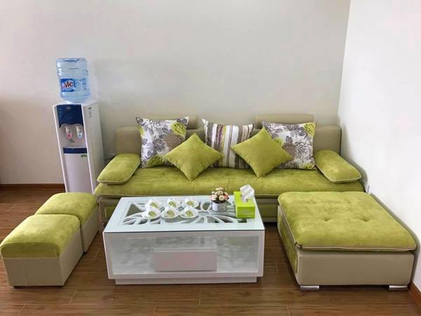 Bộ ghế sofa màu xanh, hộp giấy rút màu xanh, cả bộ ấm chén cũng có họa tiết lá xanh.