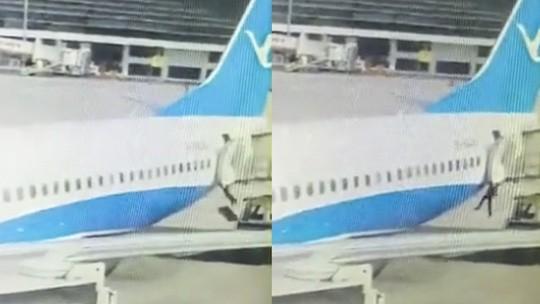 Nữ tiếp viên ngã xuống đường băng từ cửa sau máy bay. Ảnh: SCMP