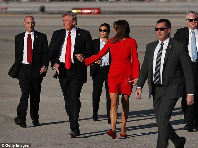 Ông Donald Trump nắm tay vợ, nhưng sau đó đột ngột buông ra để vẫy chào những người ủng hộ.