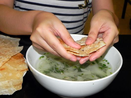 Một phần ăn dọn cho khách gồm tô nước don, bánh tráng nướng và ớt. Thực khách bẻ bánh tráng vào nước dùng rồi từ từ thưởng thức. Cách ăn này khiến nhiều thực khách lần đầu được mời tỏ vẻ ngạc nhiên.