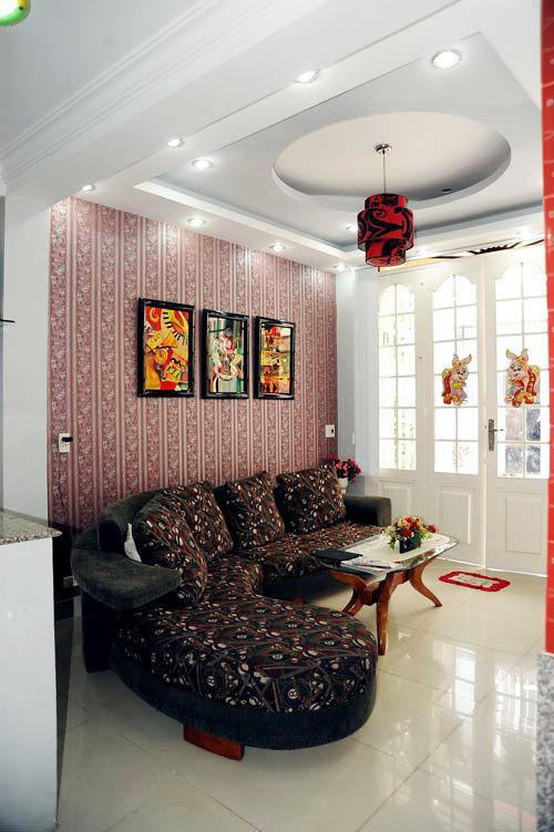 Phòng khách nhà Nguyễn Phi Hùng trông hơi rối mắt khi giấy dán tường, tranh treo tường và đệm sofa đều mang nhiều họa tiết.