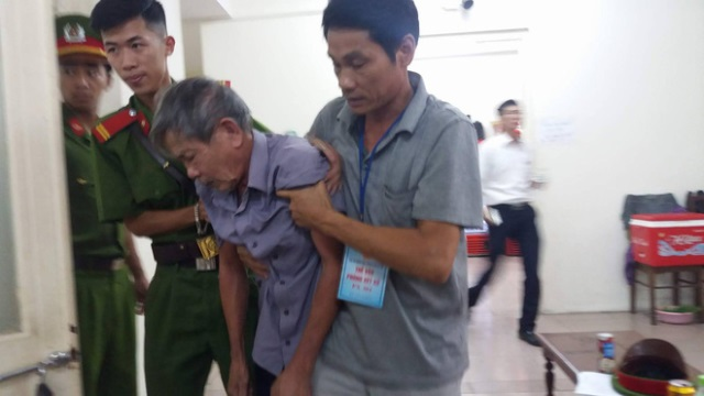 Bị cáo Nguyễn Danh Vĩnh phải nhờ sự trợ giúp của lực lượng cảnh sát hỗ trợ tư pháp mới có thể đến được vành móng ngựa. Ảnh: PV