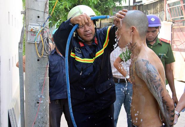 Trung tá Đinh Ngọc Đại, Đội trưởng Đội cứu nạn cứu hộ, dùng nước rửa vôi trên cơ thể nam thanh niên. Ảnh: Mai Vinh.
