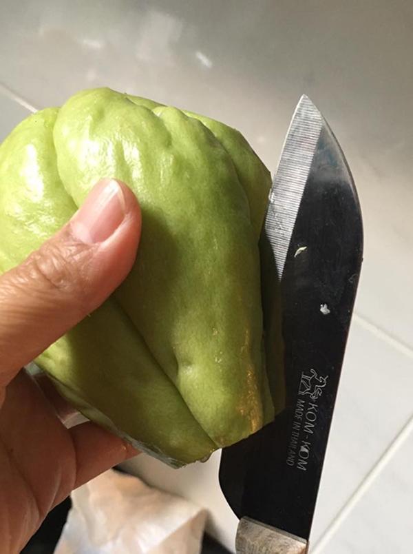 Dùng dao khoanh dọc xung quanh quả su su để tách lấy hạt. Nhẹ nhàng tách phần cùi ra, tránh làm hạt bị nứt hoặc vỡ. Nếu quả chưa há miệng, bạn có thể cắt sâu hơn vào phần đuôi vì hạt su su nằm ở phần đầu tròn.