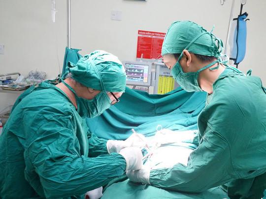 Các bác sĩ phẫu thuật đặt thanh kim loại nâng ngực cho bệnh nhân