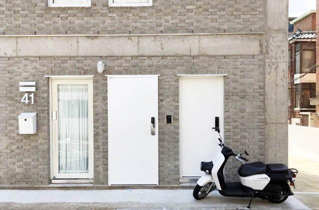 Ngôi nhà có vẻ ngoài khá mờ nhạt, nếu không nói là xấu xí với tường gạch màu ghi xám nhàm chán và kiến trúc như một khối hộp không có gì nổi bật.
