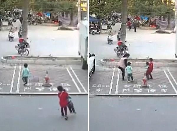 Cậu bé 7 tuổi (áo đỏ) bế em bé vào vỉa hè.
