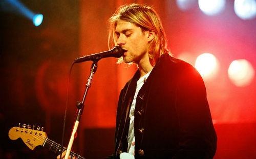"""Kurt Cobain (mất ngày 5/4/1994): Người ta tìm thấy thi thể thủ lĩnh ban nhạc Nirvana tại nhà riêng sau khi anh tự vẫn bằng súng ở tuổi 27. Kurt Cobain để lại lá thư cuối cùng gửi cho một người bạn từ thuở ấu thơ do anh tự tưởng tượng ra - người bạn có tên """"Boddah"""" - rằng mình đã không còn cảm thấy hứng thú với việc nghe nhạc hay sáng tác nhạc nữa. Trước khi tự sát, Cobain đã sử dụng rất nhiều ma túy để giải toả các cơn đau dạ dày. Anh từng có ý định tự vẫn nhiều lần nhưng bất thành."""
