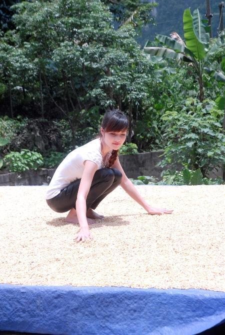Triệu Thị Hà phơi ngô trước sân.