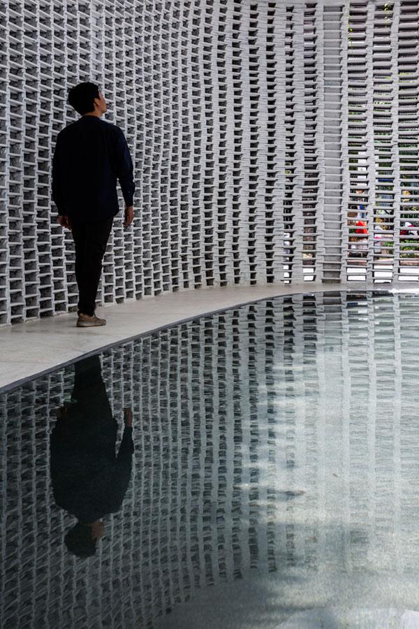Tường gạch thống gió bao quanh bể bơi.