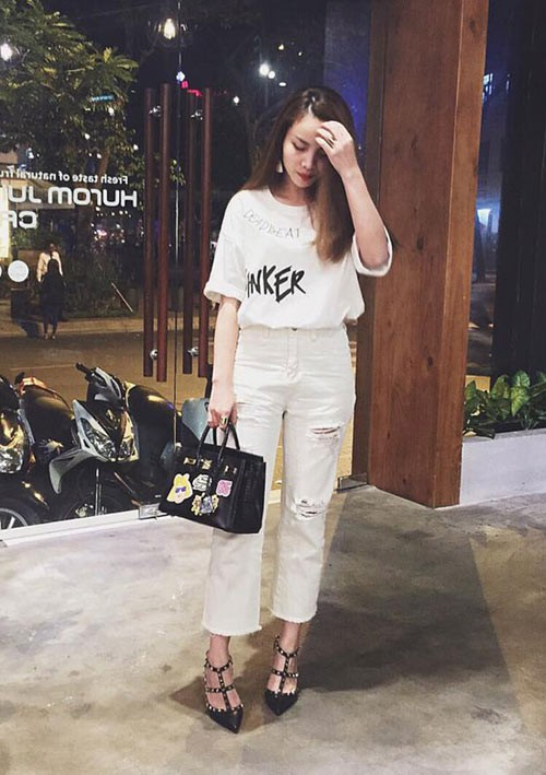 Đôi giày đinh tán màu đen cá tính, sang trọng nổi bật trên nền trang phục cây trắng của Yến Trang