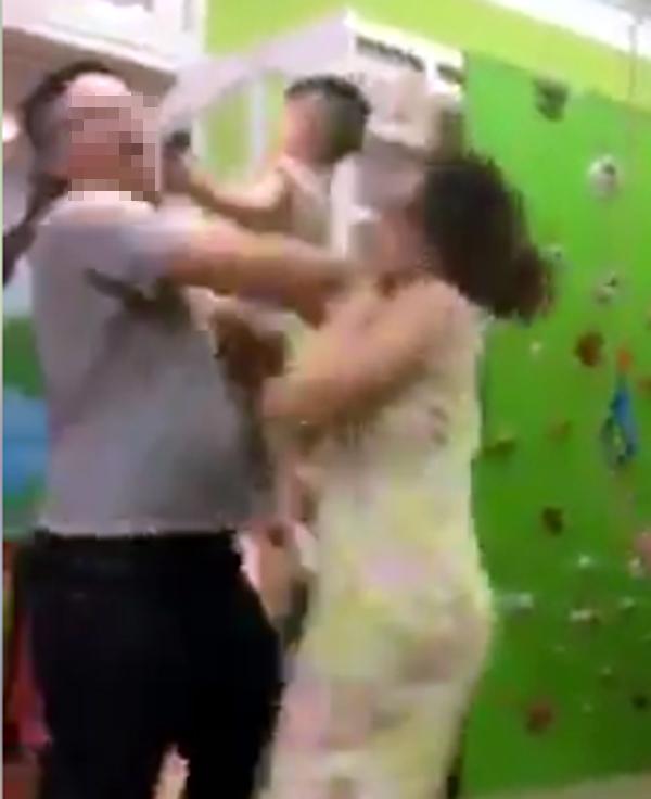 Trước khi bỏ ra cổng, người vợ tiếp tục giằng con trên tay chồng và bị chồng đánh và chửi bới.
