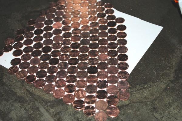 Những đồng xu sáng choang đẹp đẽ được lau khô và trải ra giấy để định hình trước cách sắp xếp trên tường.