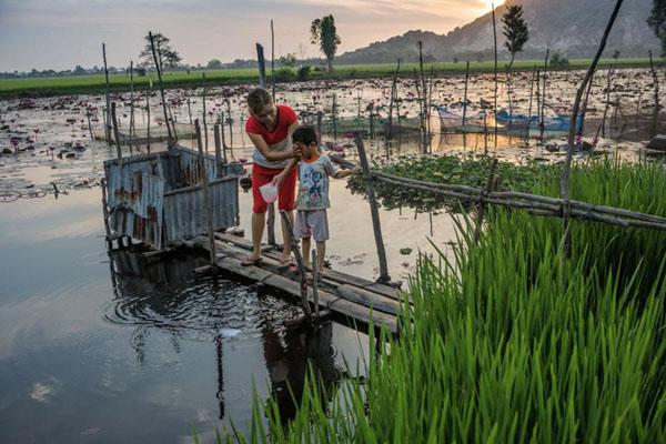 Một nhà vệ sinh dạng cầu tõm ở một vùng làng quê Nam Bộ. Một người phụ nữ đang rửa mặt cho con bằng chính nước ở đầm lầy, khá mất vệ sinh.