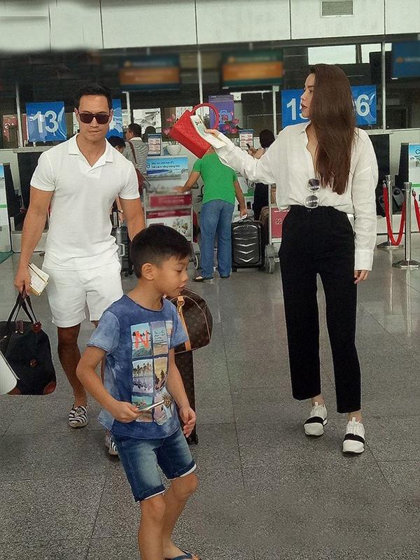 Kim Lý xách hành lý cho mẹ con Hà Hồ ở sân bay trong một chuyến du lịch.