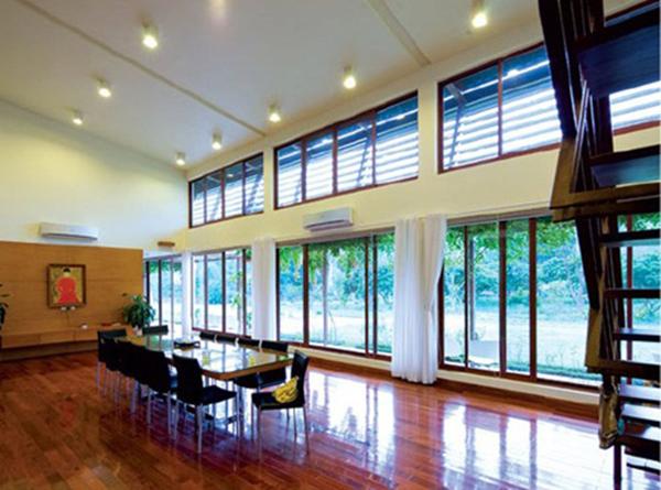 Toàn bộ tầng một đều là cửa kính sát sàn với rèm buông để có thể tận hưởng trọn vẹn khung cảnh bên ngoài. Và một chiếc bàn ăn hình chữ nhật cỡ lớn được đặt ngay gần cửa kính để có thể thưởng thức cảnh đẹp thiên nhiên tuyệt vời.