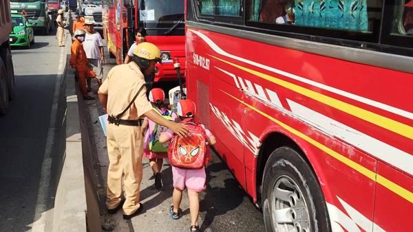 CSGT đến trấn an và đưa các em nhỏ lên một xe khách khác để tiếp tục hành trình