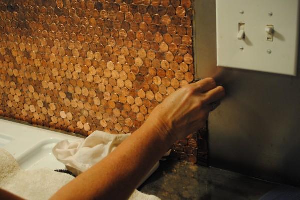 Tỉ mẩn dán từng đồng xu lên tường bằng keo silicon chống nước, chịu nhiệt.