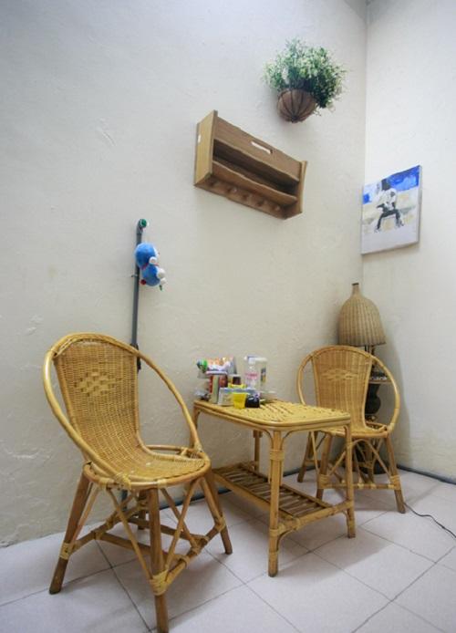 Bộ bàn ghế nhỏ xinh bằng mây tre đan để ở góc phòng với nhiều đồ ăn vặt được cô xếp bên trên.