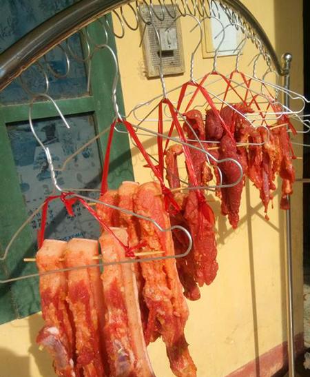 Chị Lý Thị Hạnh (Võ Nhai, Thái Nguyên) phơi thịt trên móc áo ngoài ban công. Chị Hạnh cho biết công thức của chị thêm rượu để tránh ruồi muỗi, và giúp thịt không bị ôi.