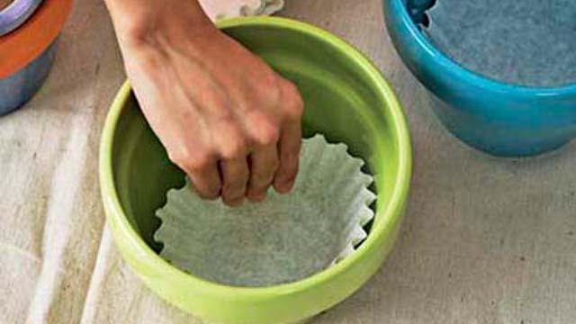 Lấy bộ lọc cà phê đã hỏng, cho thêm chút đất vào bên trong để lót đáy. Đối với nhiều loại cây trồng tránh bị úng, bạn sử dụng cách này sẽ giúp nước thoát dễ dàng hơn.