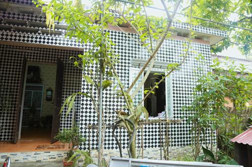 Căn nhà có mặt tiền được lát gạch men đen trắng, mái lợp ngói.