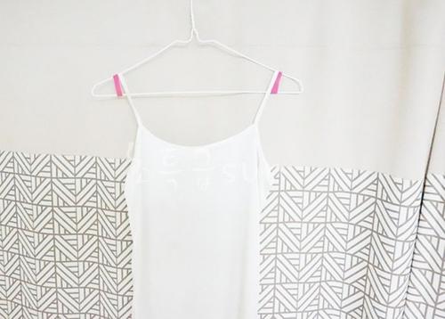 Lấy hai vòng dây cao su vừa được cắt ra lồng vào móc treo quần áo như hình, quần áo sẽ không bị tuột khi treo.