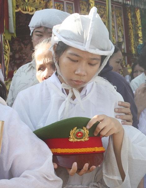 Thu Trang nâng niu chiếc mũ kê-pi của người cha anh hùng trên đường ra nghĩa trang.