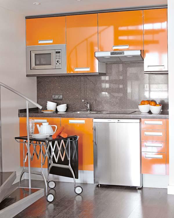 Ngay bên dưới cầu thang là một góc dùng để nấu nướng, Những chiếc tủ kệ đựng đồ kín khiến cho người ta khó có thể bóc mẽ đồ dùng trong nhà, dụng cụ nấu nướng... làm cho không gian nơi này trở nên chật hẹp. Những chiếc kệ tủ sáng choang được phủ màu cam làm không gian thêm sáng lấp lánh.