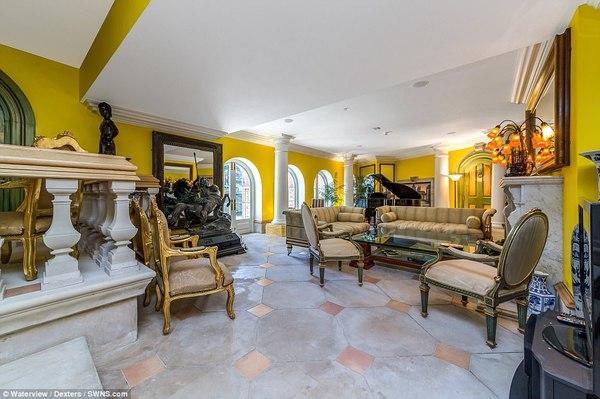 Một khu vực tiếp khách khác rộng hơn của ngôi nhà mang phong cách Hy Lạp với rất nhiều ghế ngồi được bố trí rải rác.
