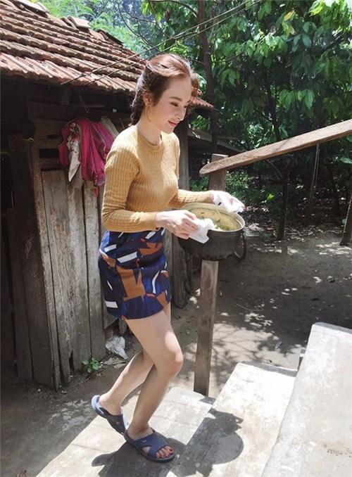 Angela Phương Trinh ăn mặc sành điệu, đi dép lê thoải mái bưng nồi thức ăn lên nhà khi về thăm quê Ngoại.