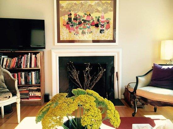 Phòng khách với hoa thơm, lò sưởi nằm trong tông màu ấm.
