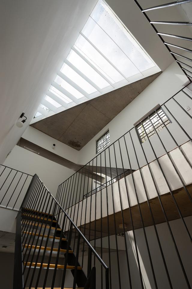 Giếng trời lớn ở cầu thang giữa nhà kết hợp với nhiều cửa sổ dọc các bức tường giúp ánh sáng lan tỏa khắp không gian sống.