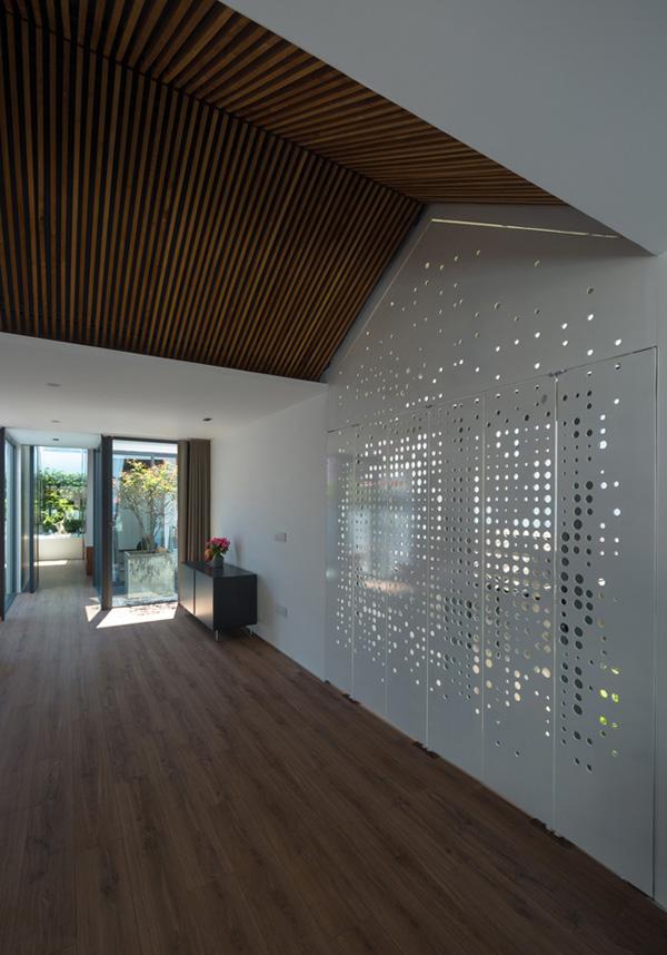 Cửa kính tạo thành một khoảng ban công nhỏ nhìn ra khu phố, mang đến sự thông thoáng cho căn phòng. Cửa kim loại đục lỗ cho ánh sáng hắt vào nhà vừa đủ mà vẫn giữ được sự riêng tư cần thiết.