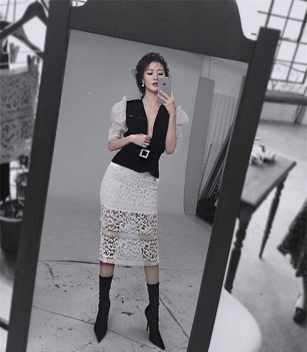 Bộ cánh trắng đen với những chi tiết tay phồng xẻ ngực sâu ôm eo được cô nàng phối cực chuẩn cùng đôi sock boots, hợp tông đến từng chi tiết