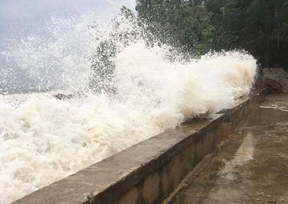 Những đợt sóng mạnh tràn qua mặt đê Quỳnh Long. Ảnh: Quang Hợp